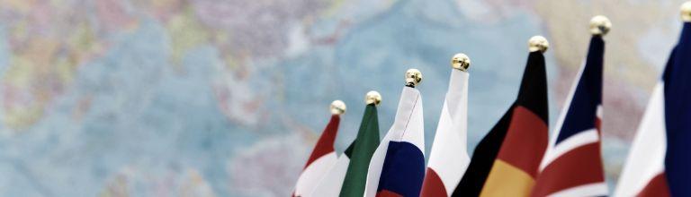 Flaggen der G7 vor einer Weltkarte